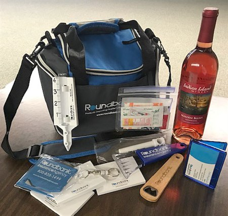 Donated by Roundbank Insurance. 6-pack soft-side cooler, Indian Island Maiden Blush wine, rain gauge, big clip, bottle opener, ice scraper, sticky notes, key ring, letter opener, sun & fun emergency kit.
