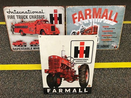 Reproductions of Farmall and iH tractor advertising signs.